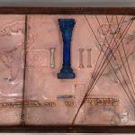 Anna Bella Geiger, Orbis Descriptio em fronteiras indiferentes, série Fronteiriços, Gaveta de arquivo de ferro, encaustica, molas de aço e fios de cobre, 10 x 61 x 44 cm, 1999.