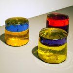 Amélia Toledo, A onda, Cilindro de PVC com liquido e óleo coloridos, 10 x 10 cm, múltiplo